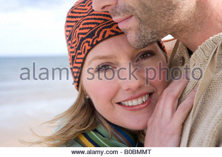 Young couple embracing on beach, close-up of woman smiling, portrait Banque D'Images