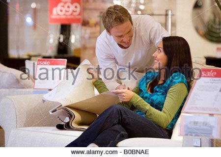 Jeune couple avec échantillons de tissus dans la boutique, smiling at each other Banque D'Images