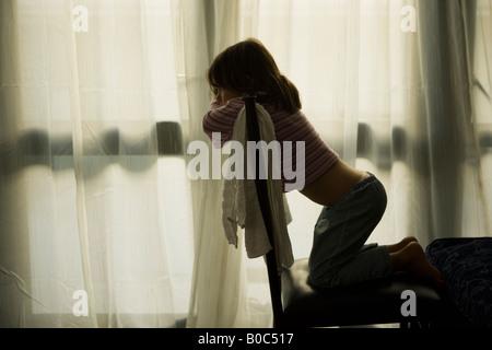 Jeune fille âgée de quatre s'agenouille sur chaise et regarde la télévision dans une chambre de motel Banque D'Images