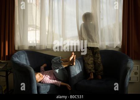 Garçon de 6 ans regarde la fille âgée de quatre fenêtres est assis dans un fauteuil de motel Wellington New Zealand Banque D'Images