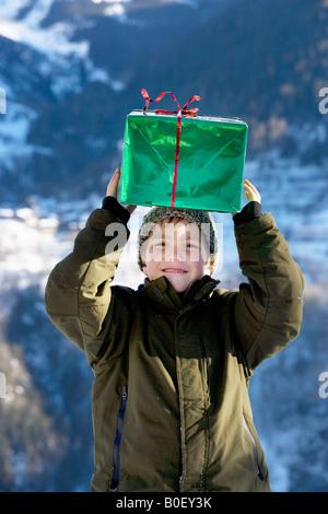 Garçon avec présents dans la neige Banque D'Images