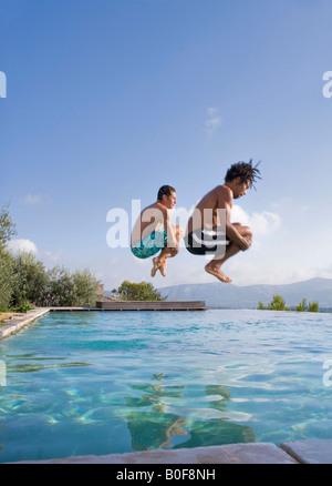 Les jeunes hommes de sauter dans une piscine Banque D'Images