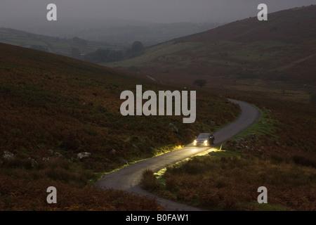 Mercedes voiture conduit le long d'une route de campagne de nuit le Dartmoor Devon Royaume Uni Banque D'Images