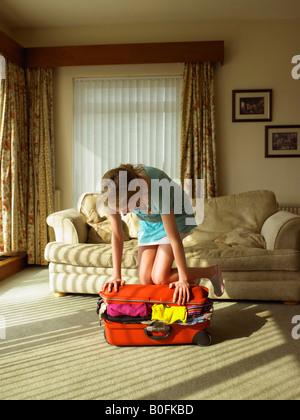 Jeune femme essayant de fermer suitcase Banque D'Images
