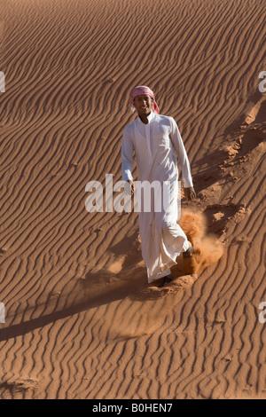 Bedouin descendre une dune de sable, de rides, de rire, Wadi Rum, Jordanie, Moyen-Orient Banque D'Images