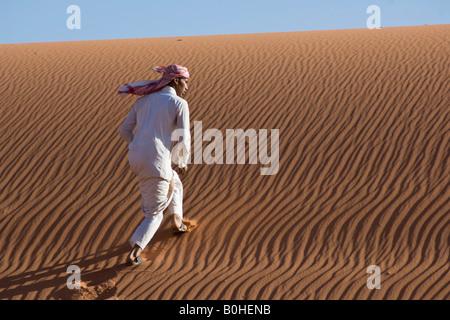 Bedouin l'ascension d'une dune de sable, de rides, Wadi Rum, Jordanie, Moyen-Orient Banque D'Images