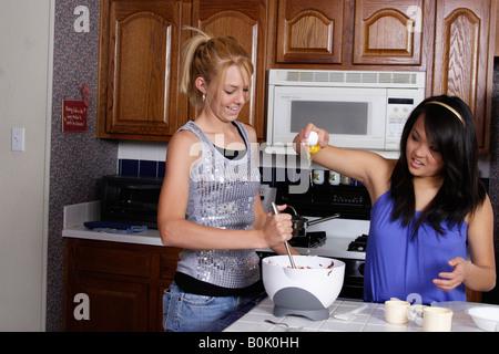 Stock photo de deux adolescentes dans la cuisine s'amusant faire brownies Banque D'Images
