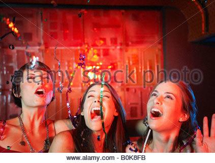 Trois femmes dans une discothèque de boire et de rire Banque D'Images