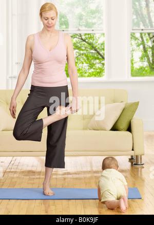 Mère faisant du yoga près de bébé garçon Banque D'Images