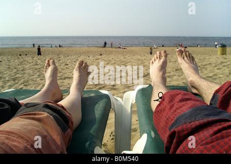 Deux amant couple homme femme couchée sur le siège d'autres plage plage de Scheveningen Den Haag Pays-Bas summer Banque D'Images