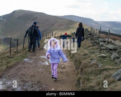 Jeune fille et sa famille le sentier de marche plus de Mam Tor. Parc national de Peak District. UK Banque D'Images
