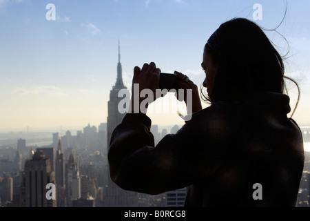 Femme photographiant l'empire state building Banque D'Images