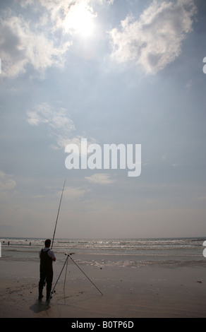 Silhouette of man seafishing partielle sous le soleil chaud et bleu ciel nuageux sur inch strand beach County Kerry, péninsule de Dingle
