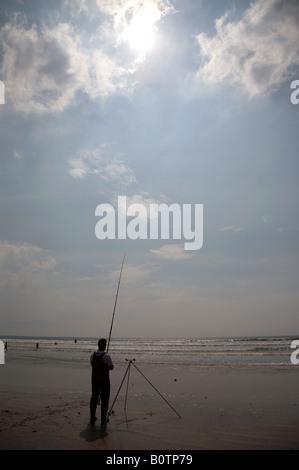 Silhouette of man seafishing partielle sous le soleil chaud et bleu ciel nuageux sur inch strand beach County Kerry, Banque D'Images