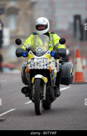 Service de police d'Irlande du PSNI agent moto en patrouille le port de casque de la conduite dans le centre-ville Banque D'Images