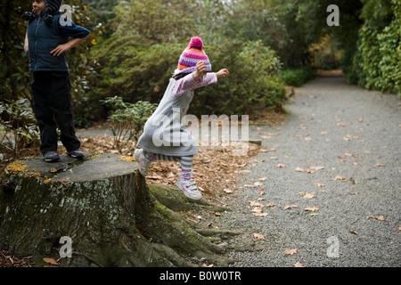 Garçon de 6 ans et sa sœur âgée de 4 ans se relaient sautant d'une souche d'arbre