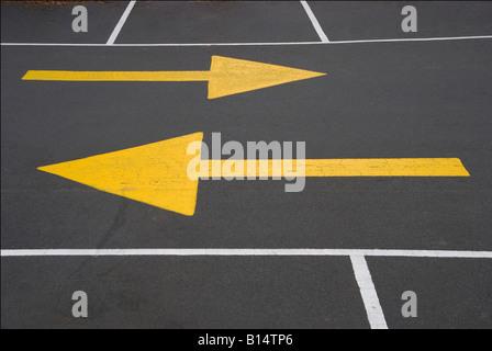Marquage directionnel jaune pointant dans des directions opposées Banque D'Images