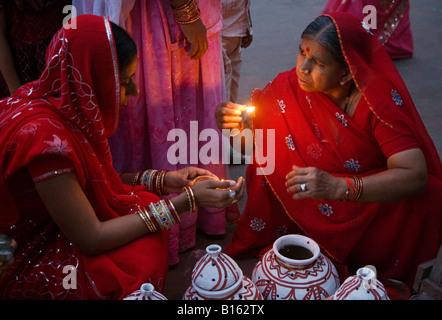 Les femmes du Rajasthan placer une bougie dans un pot en argile dans le cadre du festival à JOHDPUR GANGUR RAJASTHAN Banque D'Images