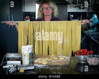 Woman holding up poteau avec des pâtes qui s'accrochent à lui Banque D'Images