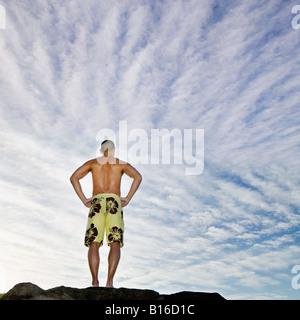 Vue arrière de l'Asian man with hands on hips Banque D'Images