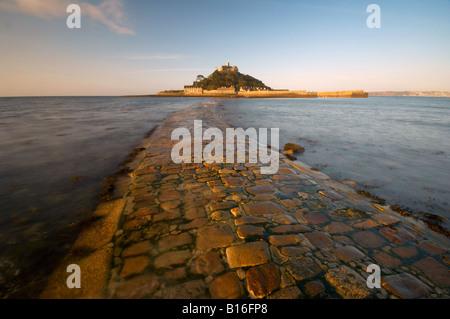 Se précipitant sur les vagues de l'ancienne chaussée en pierre menant à St Michaels Mount à l'aube Cornwall Marazion UK