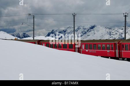 Wagons de train rouge vif apparaissant de pentes des montagnes couvertes de neige dans les Alpes suisses. Plein Banque D'Images