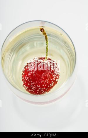 Cherry et bulles dans le verre à champagne, high angle view