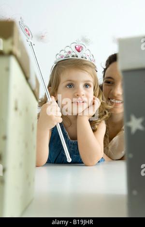 Petite fille vêtue comme une princesse, la main sous le menton, à l'écart Banque D'Images