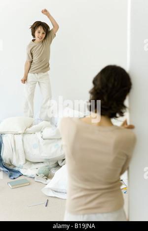 Petit garçon sautant sur lit défait, mère regarder à partir de la porte
