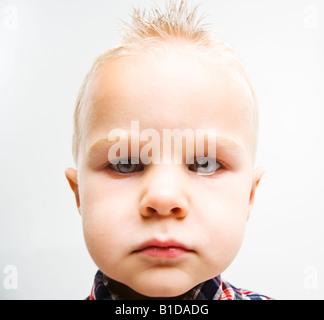 Petit garçon blond blanc avec des cheveux, avec un ballon spikey stare en colère à l'appareil photo Banque D'Images