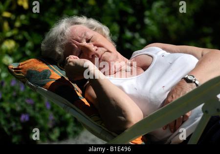 Une dame BRITANNIQUE PENSIONNÉ BÉNÉFICIE D'une journée ensoleillée le soleil DORMIR DANS LE CONTENU DE RETRAITE Banque D'Images