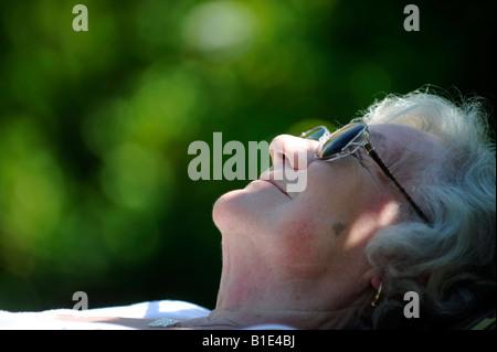 Une vieille dame BRITANNIQUE PENSIONNÉ BÉNÉFICIE D'une journée ensoleillée à dormir dans un bain de soleil RELAXANT Banque D'Images