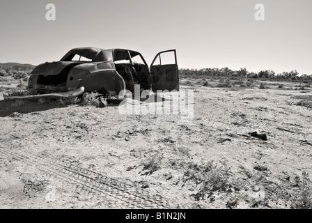 Image en noir et blanc d'une vieille voiture rouillée dans le désert Banque D'Images