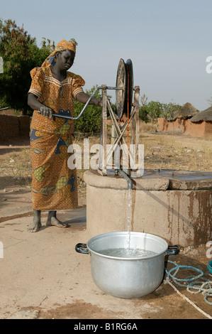 Woman getting l'eau d'un puits à roues, colis, Cameroun, Afrique