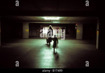 Femme et enfant marche dans parking souterrain éclairé par une lumière fluorescente Banque D'Images