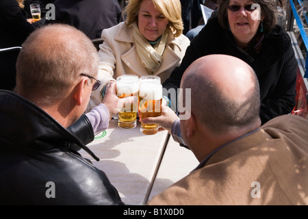 Deux couples toast avec une bière au restaurant rue table dans Markt, à Delft. Aux Pays-Bas. Banque D'Images