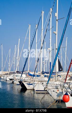 Vue verticale à travers une marina animée avec beaucoup de yachts coûteux amarré dans une rangée aux côtés de la Banque D'Images
