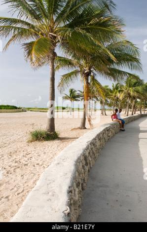 Couple sous les palmiers dans le parc Lummus dans South Beach Miami Banque D'Images