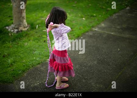 Jeune fille âgée de 4 ans apprendre à aller noter trademarked Disney la corde à sauter Banque D'Images