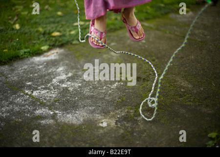 Jeune fille âgée de 4 ans apprendre à sauter Banque D'Images