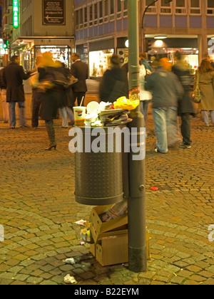 Corbeille ordures poubelle et une poubelle pleine poubelle dans la zone piétonne de la nuit dans la ville Frankfurt Banque D'Images