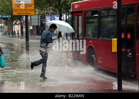 Homme d'être éclaboussé par un bus passant à Lewisham High Street sur un très mauvais jours Banque D'Images
