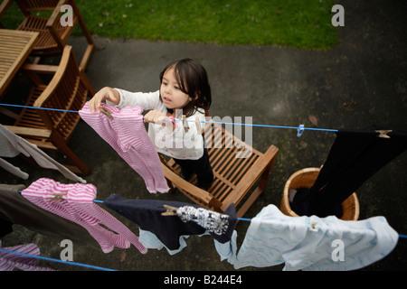 Étendre le linge sur l'étendoir pour sécher fille âgée de cinq et six frère Banque D'Images
