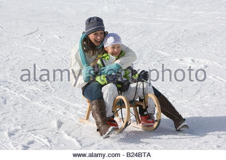 Une mère et une fille à cheval sur un traîneau Banque D'Images