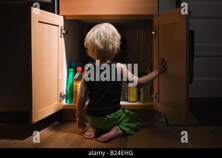 Petit garçon ouvrant placard de produits de nettoyage Banque D'Images