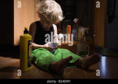 Petit garçon avec les produits de nettoyage Banque D'Images