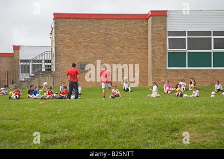Le Nord du Pays de Galles Royaume-uni juillet un groupe de jeunes enfants d'âge scolaire ayant une leçon sur les jeux de l'activité sur le terrain de l'école essaie de battre l'obésité chez les enfants