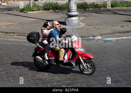 Man rides moto avec ses enfants et les pourparlers sur téléphone mobile à Catane, Sicile, Italie Banque D'Images