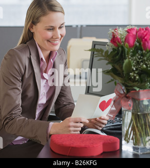 Businesswoman reading Valentine's Day card Banque D'Images