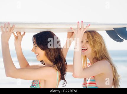 Deux femmes holding surfboard on chefs Banque D'Images